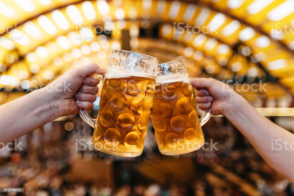 two hands clinking beer glasses in octoberfest marquee - foto de acervo
