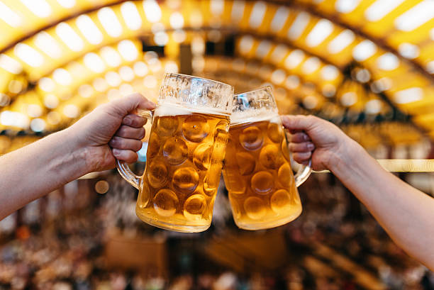 two hands clinking beer glasses in octoberfest marquee - german culture stock pictures, royalty-free photos & images