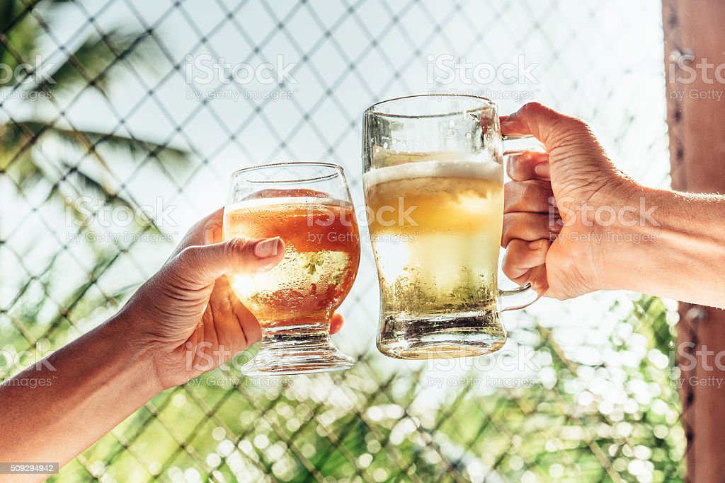 two hands clinking beer glasses in tropic sun light