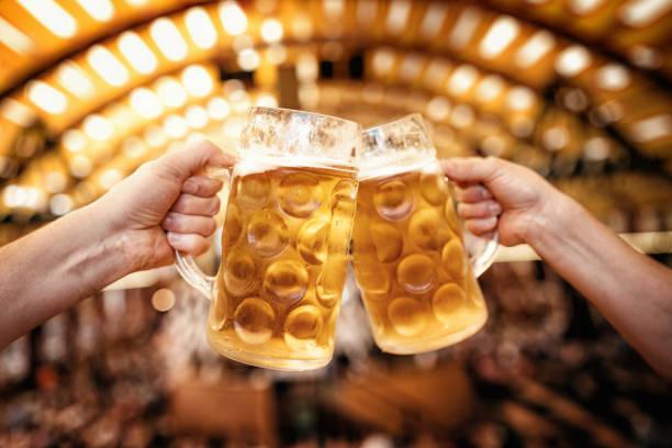 zwei Hände klirrendes Masse-Biergläser auf dem Oktoberfest in München – Foto