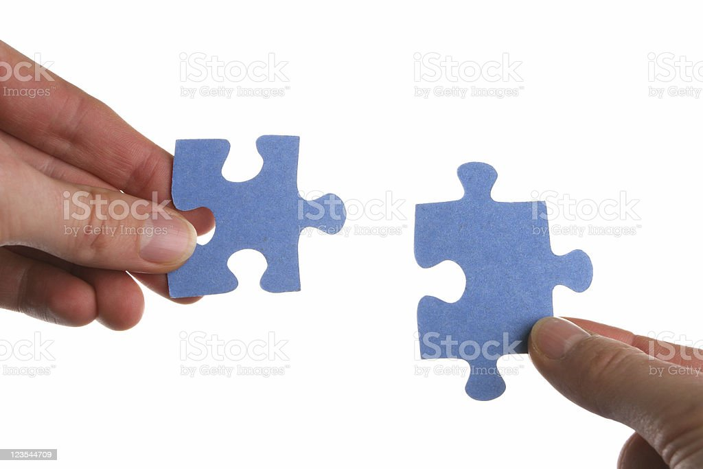 Two hands coming together to solve a puzzle stock photo