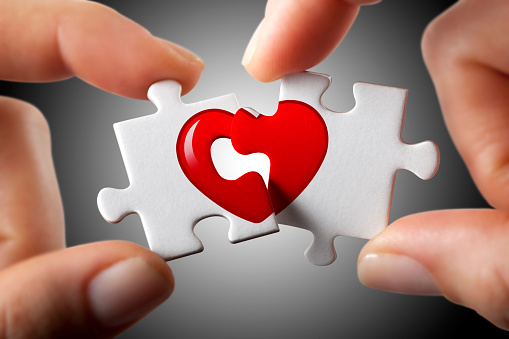 Two woman hands connecting or separating two puzzle pieces with the heart symbol.