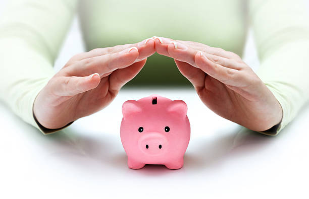 Two hands covering a small pink piggy bank to protect it concept of financial protection - with woman shielding stock pictures, royalty-free photos & images