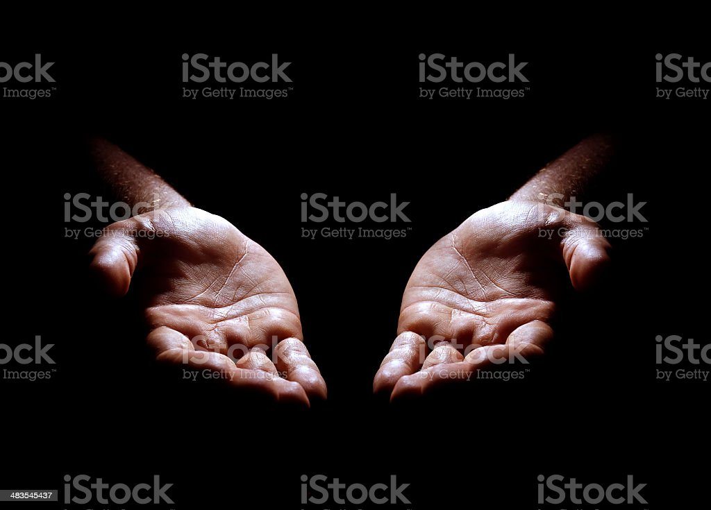 Two hands emerging from the darkness stock photo