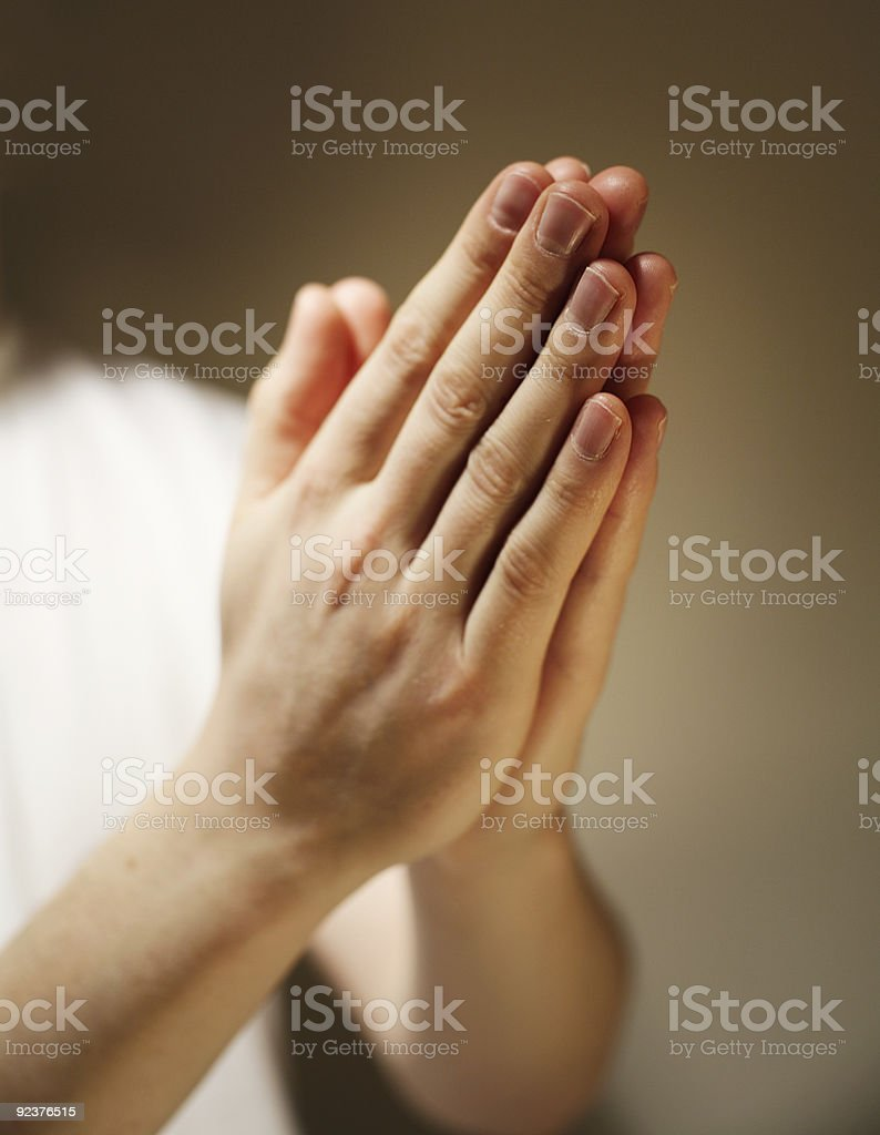Two hands folder in prayer in front of a brown background royalty-free stock photo