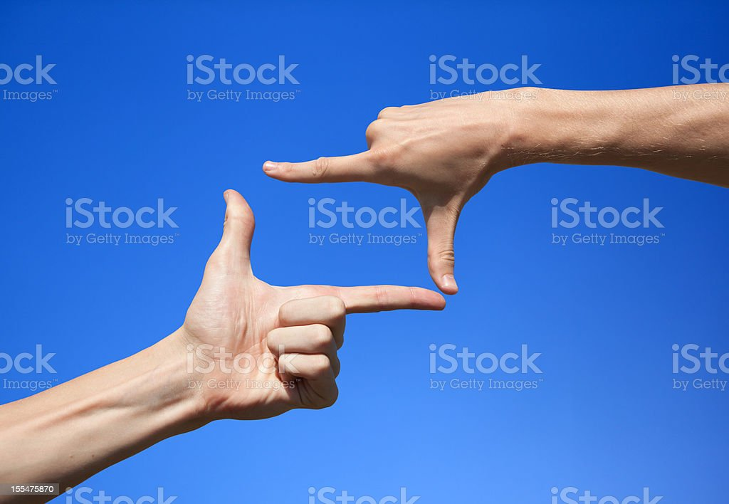 Two hands forming a square frame over blue background stock photo