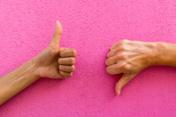 two hands giving thumbs up and thumbs down against pink background - thumbs down stock photos and pictures