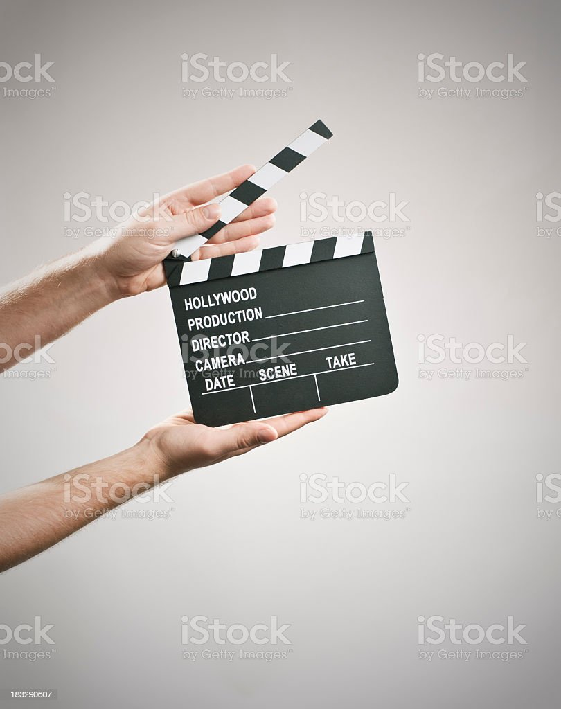 Two hands holding a clapperboard on a white background stock photo