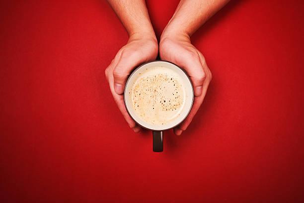 zwei hände halten einer tasse frischen kaffee - rotes oberteil stock-fotos und bilder