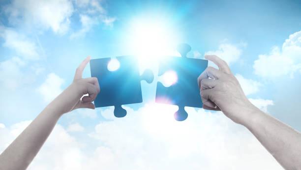 zwei hände halten ein puzzleteil über blauen himmel hintergrund und sonne. business, support, das richtige entscheidungskonzept finden. - twilight teile stock-fotos und bilder