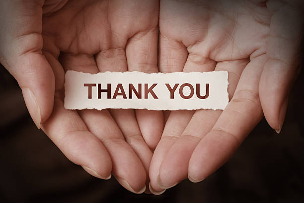 Two hands holding a small thank you note stock photo