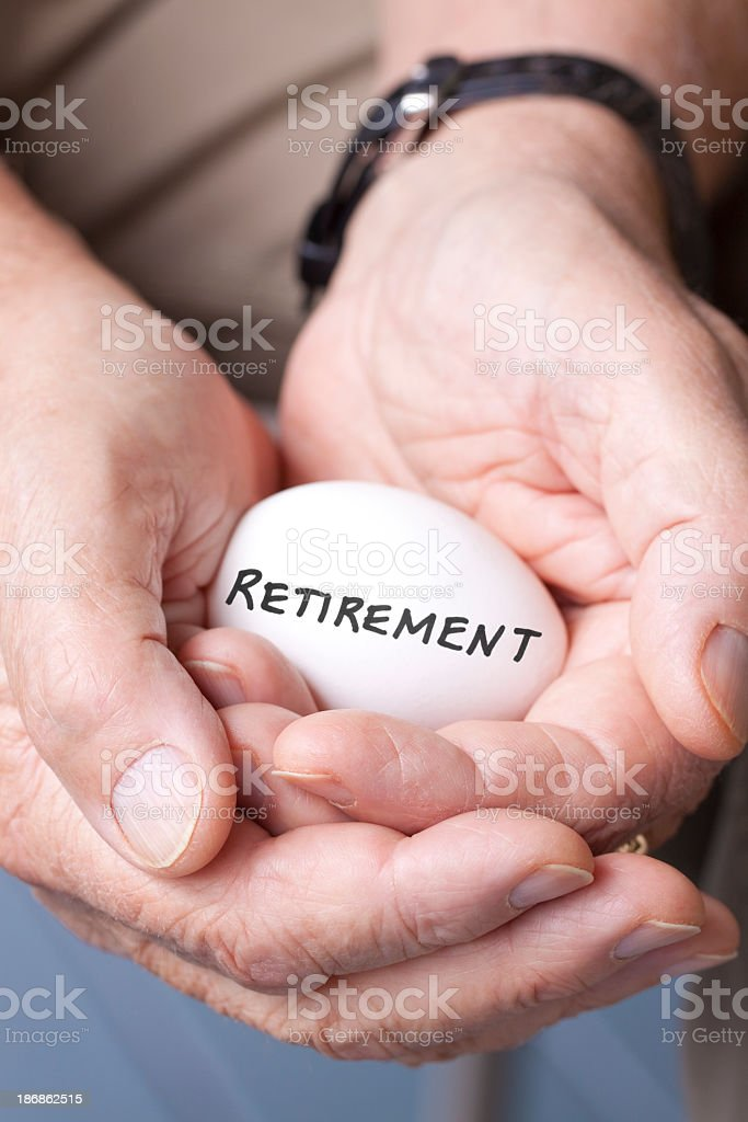 Two hands holding an egg with retirement written on it royalty-free stock photo