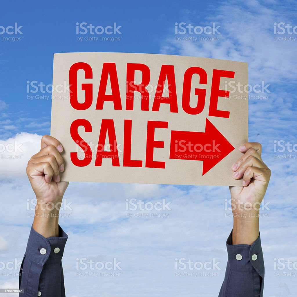 Two hands holding brown cardboard with garage sale stock photo