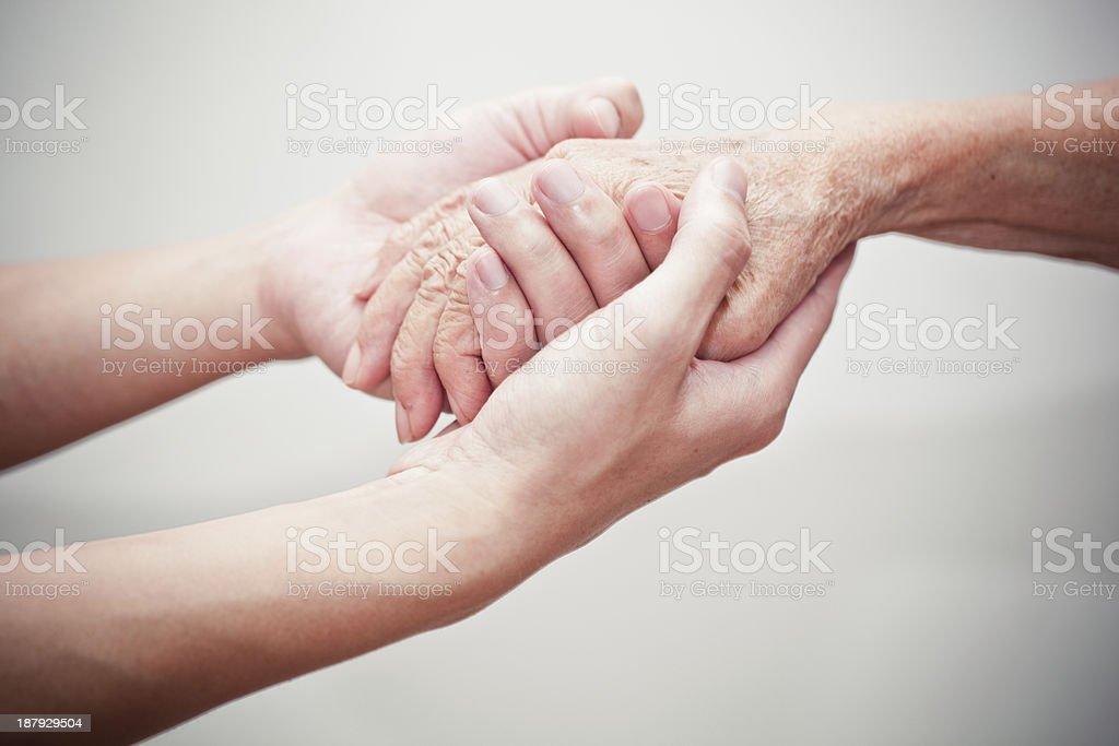 Zwei Hände halten hand eines älteren person – Foto
