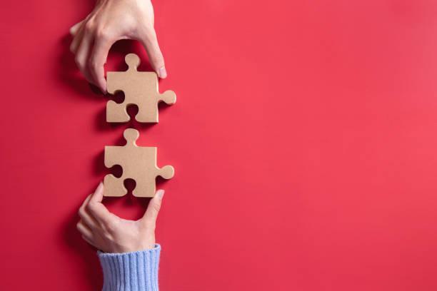 two hands holding jigsaw, concept for teamwork building a success. - coinvolgimento dei dipendenti foto e immagini stock