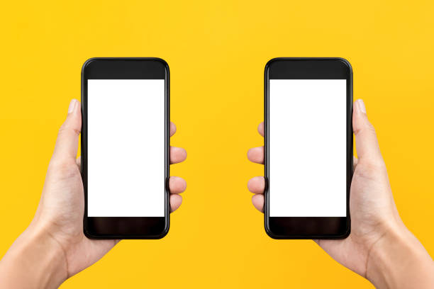 Two hands holding mobile phones on yellow background with empty screens stock photo