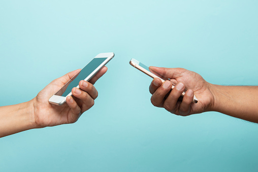 Man and woman holding smart phones on blue background.