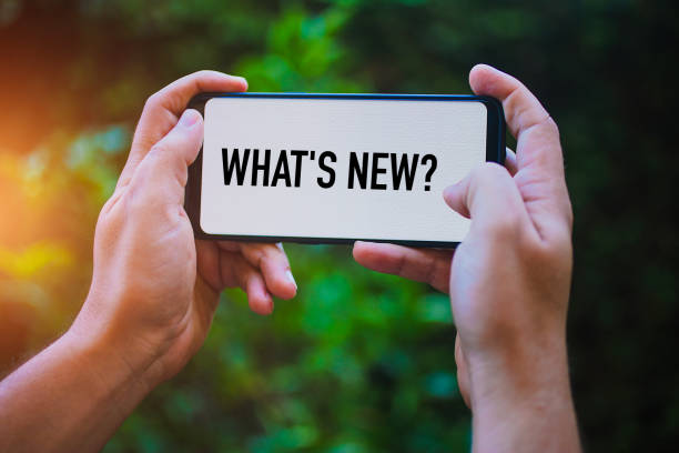 Two hands holding modern smartphone with the text : What's New? stock photo