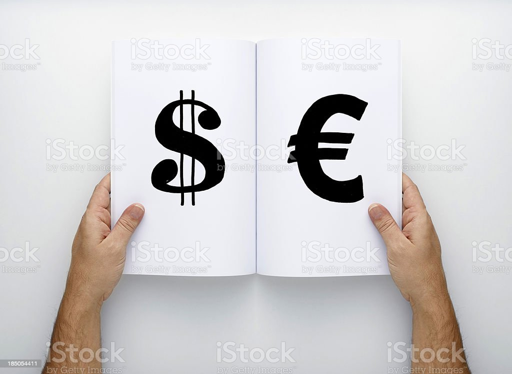 Two Hands Holding Open Magazine, write Dollar and Euro sing royalty-free stock photo