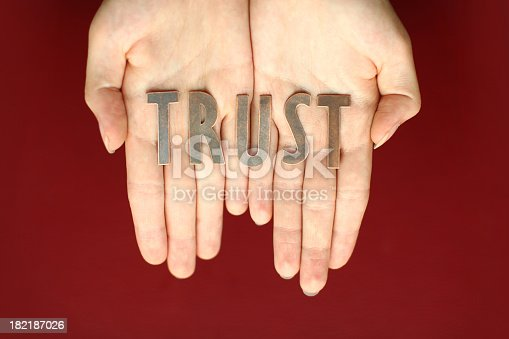Hands Holding Word Trust on a Red Background. XL, Canon 5D Shallow Depth of Field