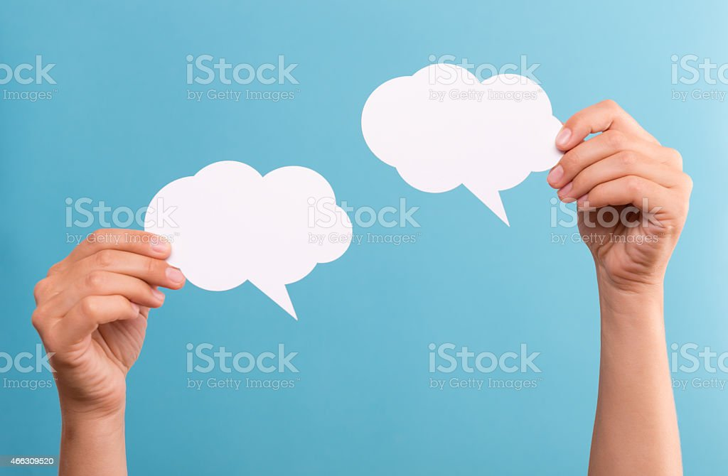 Two hands holding up two speech bubbles stock photo