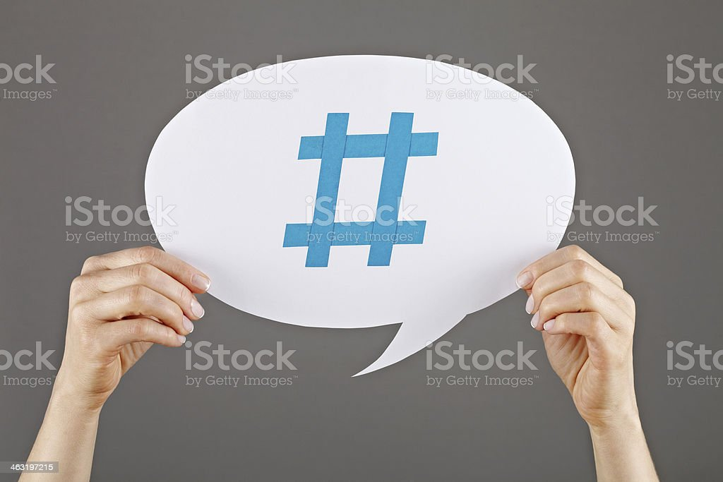 Two hands holding up white speech bubble with hashtag stock photo