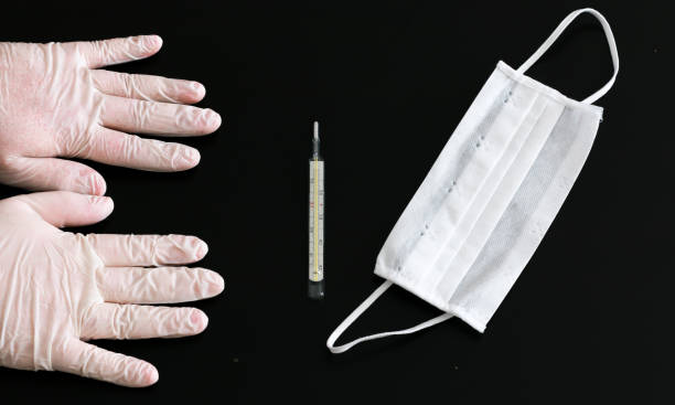 Two hands in latex gloves, thermometer and medical mask close-up stock photo