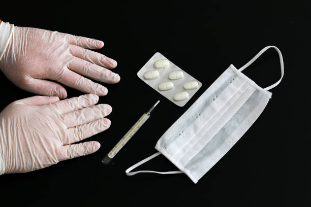 Two hands in latex gloves, thermometer, tablets and medical mask stock photo