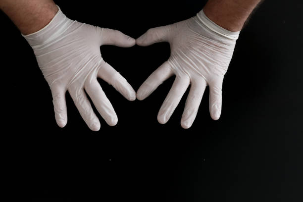 Two hands in medical gloves show heart shape on black background stock photo