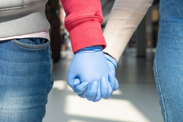 Two hands in rubber gloves holding each other. stock photo