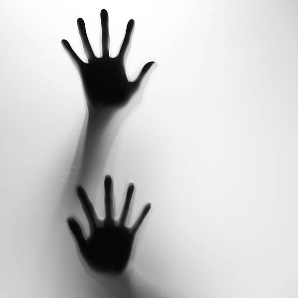 Two hands in silhouette pressed against frosted glass stock photo