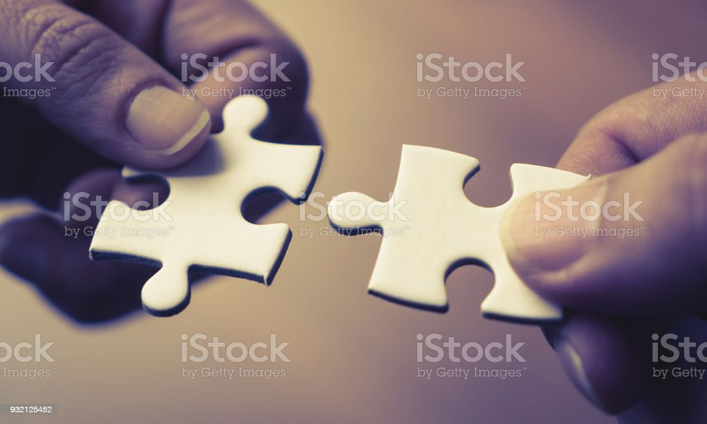 Two Hands Joining Together Two Jigsaw Puzzles Stock Photo