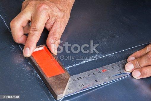 istock Two hands keep metal angle on steel plate. 922890348