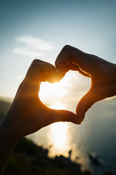 Two hands making heart shape in sky stock photo