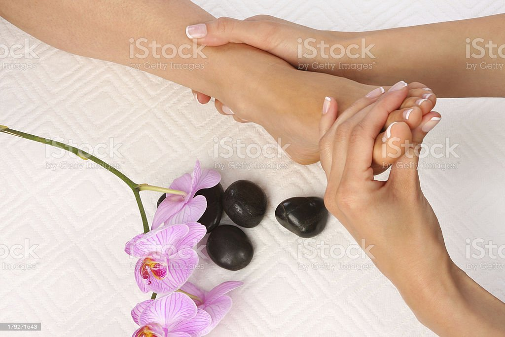 Two hands massaging a foot next to smooth stones and flowers stock photo