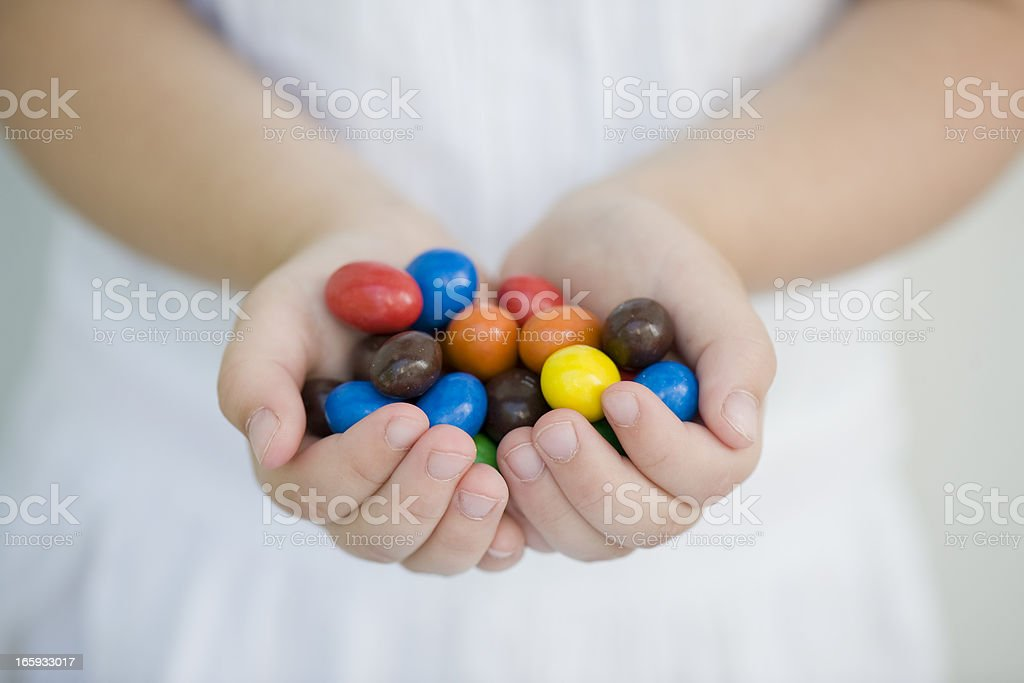 Two hands of a child holding colorful candies royalty-free stock photo