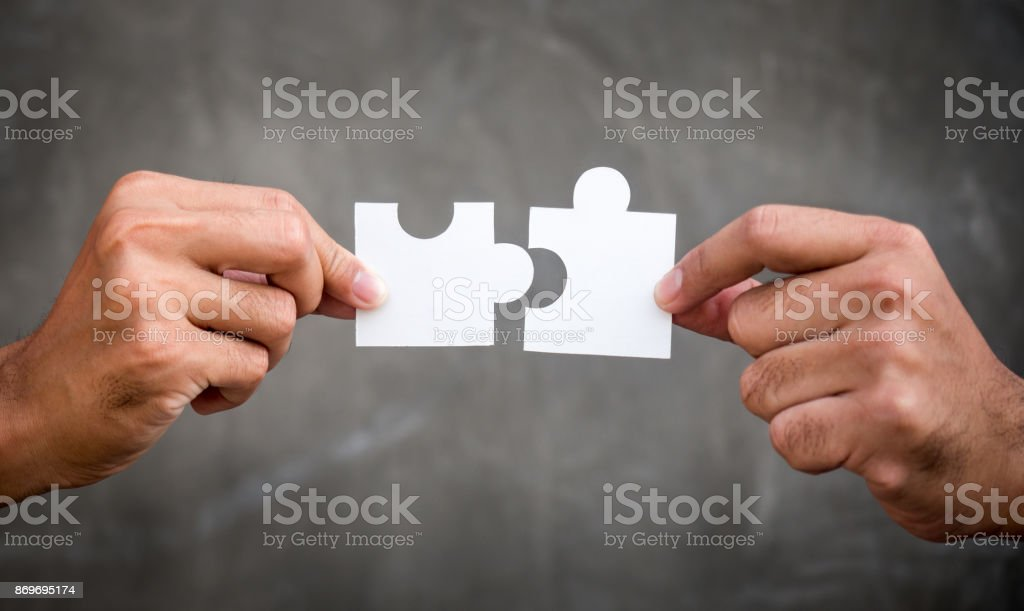 Two hands of businessman holding jigsaw/puzzle for teamwork cooperation and togetherness concept - Foto stock royalty-free di Accordo d'intesa