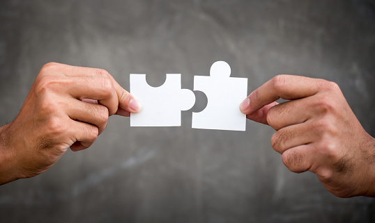 Two Hands Of Businessman Holding Jigsawpuzzle For Teamwork Cooperation And Togetherness Concept - Fotografie stock e altre immagini di Accordo d'intesa