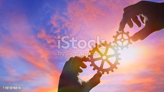 Two hands of businessmen assemble gears into a puzzle. Business concept idea, cooperation, partnership, teamwork. Copy space