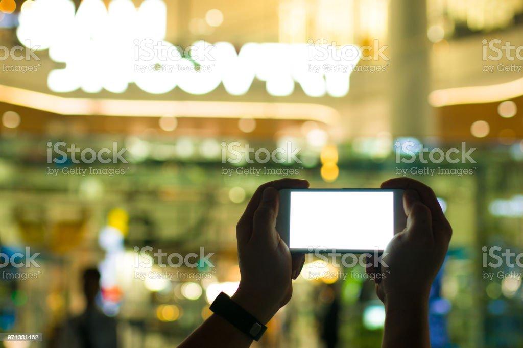 Duas mãos de homem jogando smartphone com monitor branco brilhante sobre fundo colorido bokeh para Oi conceito de tecnologia que parecem avançam a vida na cidade - foto de acervo