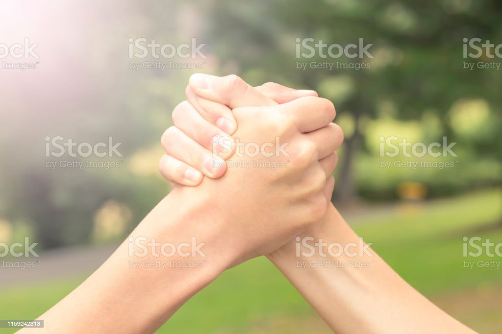 Two hands of teenagers are fighting among themselves in the park and...