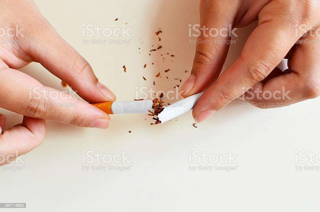 Duas mãos de mulher últimas um cigarro isolada no branco