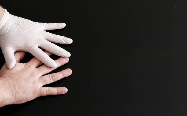 Two hands on a black background. One hand in a medical glove. stock photo