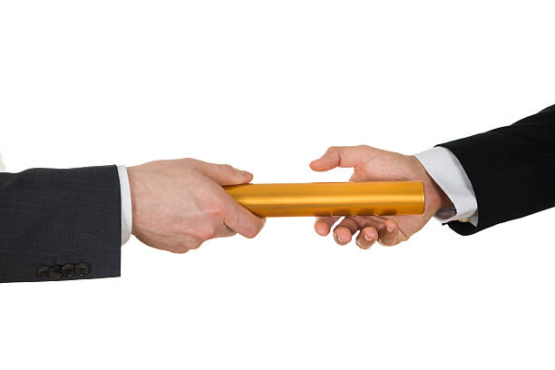 zwei hände übergeben einer goldenen staffelstab - staffelstab stock-fotos und bilder