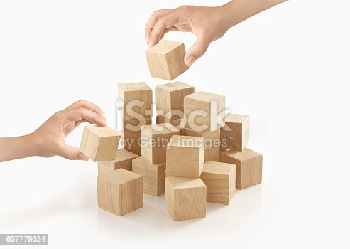 657779378 istock photo Two hands playing wooden box on isolated background. 657779334