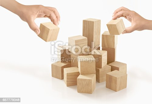 657779378 istock photo Two hands playing wooden box on isolated background. 657779348