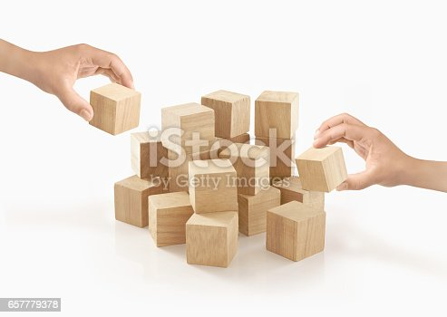 istock Two hands playing wooden box on isolated background. 657779378