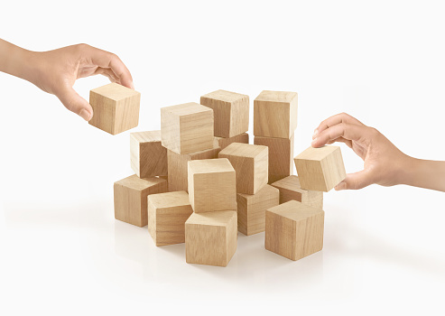 Two hands playing wooden box on isolated background.