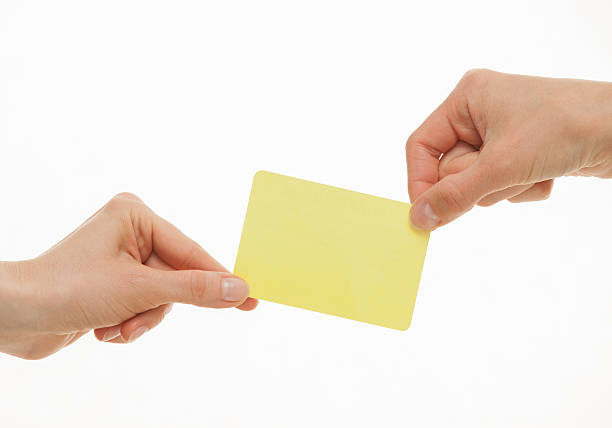 zwei hände ziehen in verschiedene richtungen eine gelbe karte - karte ziehen stock-fotos und bilder
