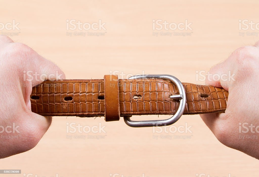 Two hands pulling a leather belt stock photo